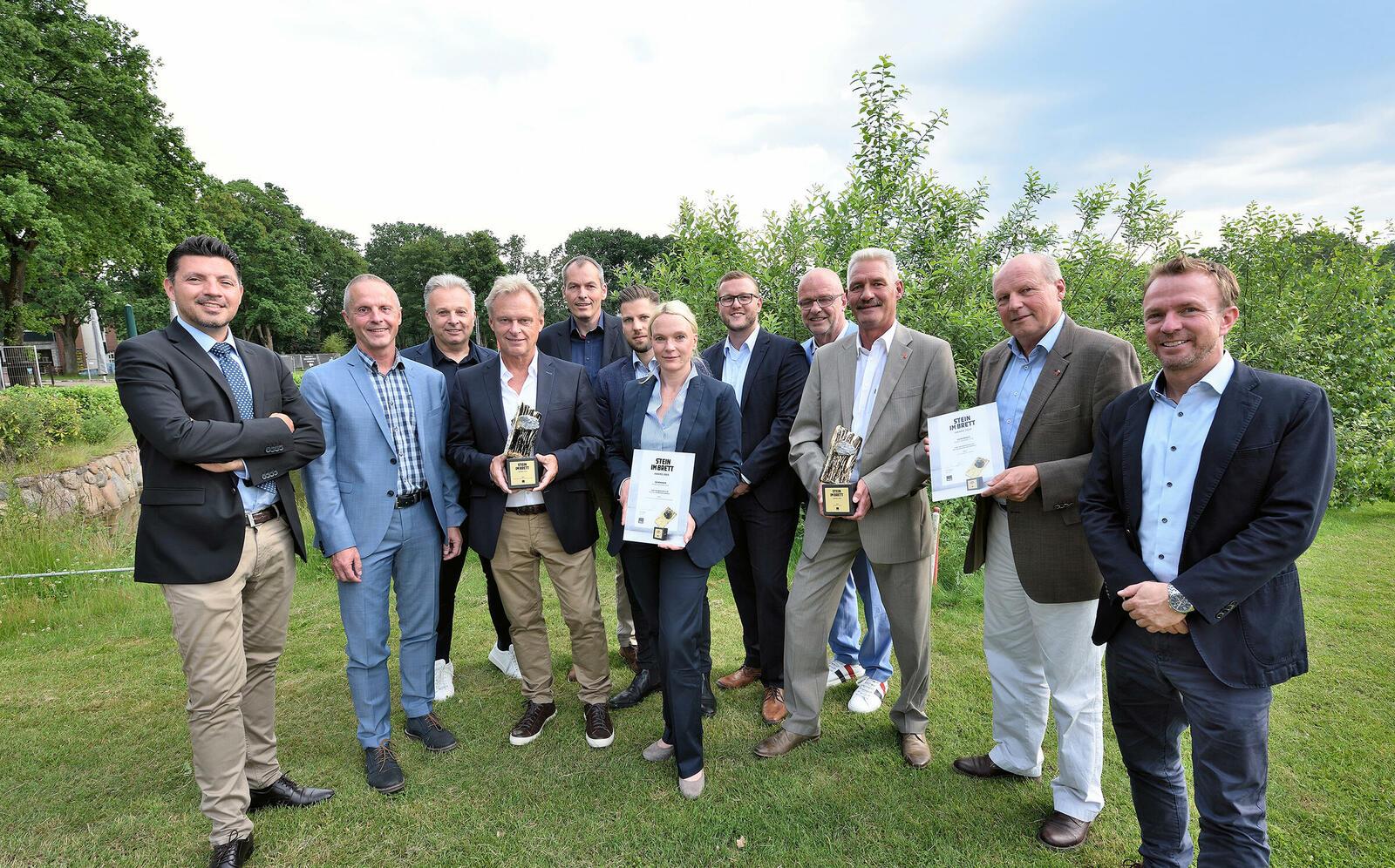 Stolz präsentiert die Aco-Mannschaft die Awards.